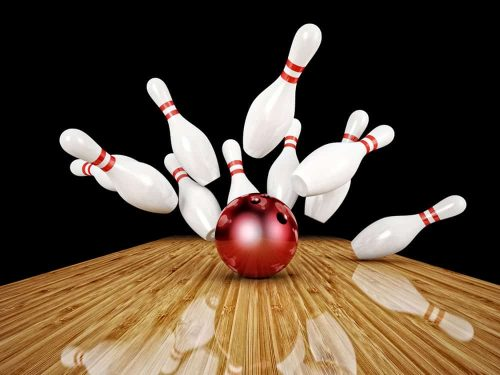 Bowling pins being scattered by ball